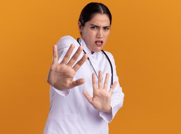 Jonge vrouw arts in medische jas met een stethoscoop om haar nek kijken naar voorkant bang maken defensie gebaar met handen permanent over oranje muur