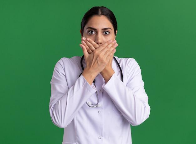 Jonge vrouw arts in medische laag met stethoscoop die voorzijde bekijkt die wordt geschokt die mond behandelt met handen die zich over groene muur bevinden