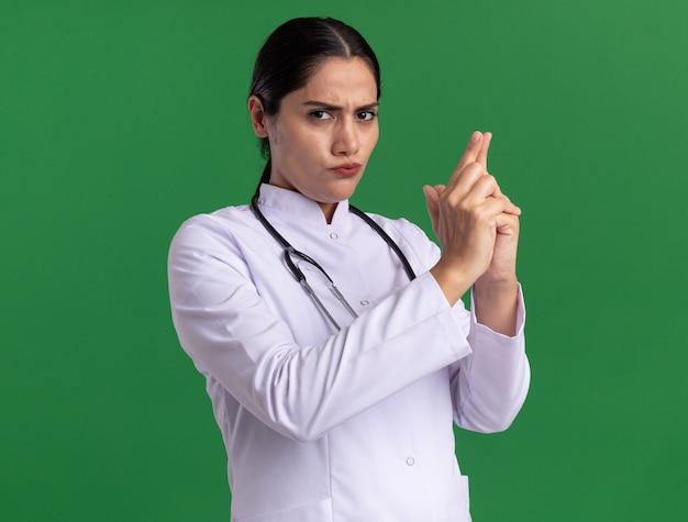 Jonge vrouw arts in medische vacht met stethoscoop die voorzijde met ernstig gezicht bekijkt die pistoolgebaar met vingers maakt die zich over groene muur bevinden