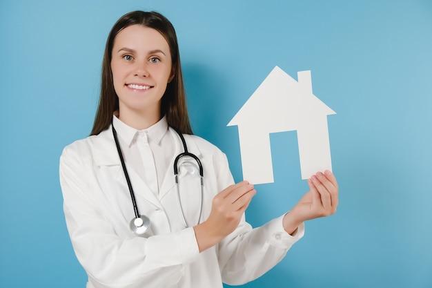 Jonge vrouw arts in professionele medische witte uniform en stethoscoop houdt klein papieren huis, kijkend naar camera glimlachen, poseren geïsoleerd op blauwe achtergrond. zorgverzekeringsconcept