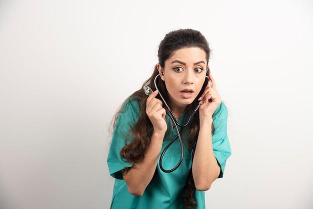Jonge vrouw arts in uniform met stethoscoop.