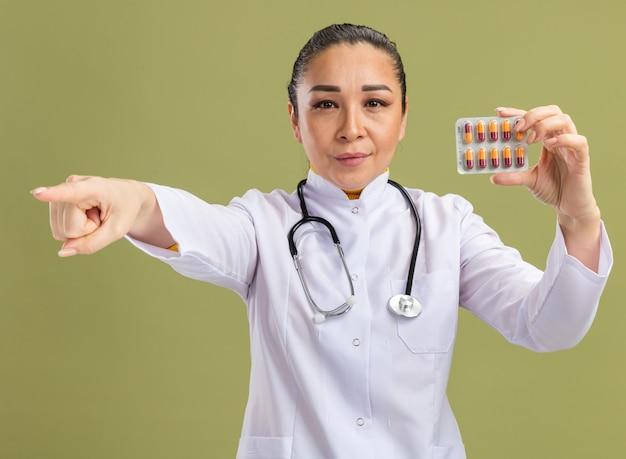 Jonge vrouw arts in witte geneeskunde jas met stethoscoop om nek houden blister met pillen camera kijken met ernstig gezicht wijzend met wijsvinger naar iets op groene muur
