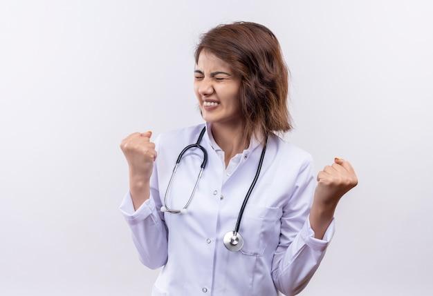 Jonge vrouw arts in witte jas met een stethoscoop balde vuisten met geïrriteerde uitdrukking