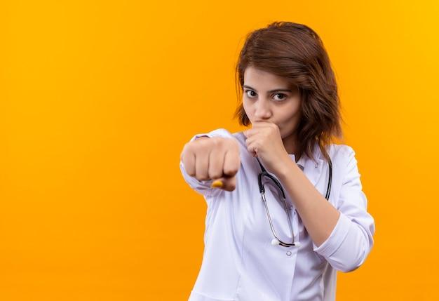 Jonge vrouw arts in witte jas met een stethoscoop clanching vuist naar camera ermee