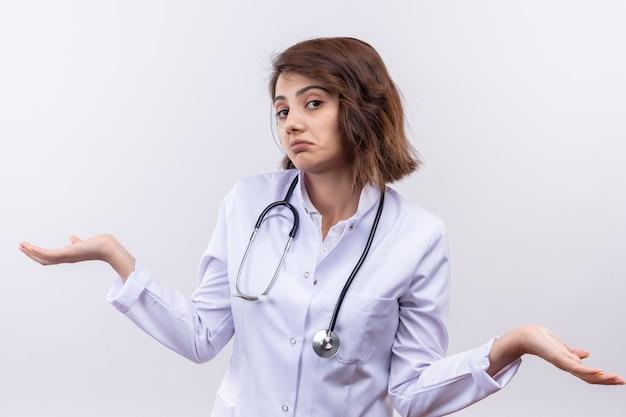 Jonge vrouw arts in witte jas met stethoscoop op zoek onzeker en verward schouders ophalen zonder antwoord