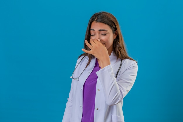 Jonge vrouw arts in witte laag met phonendoscope die zich met gesloten ogen bevinden die adem met vingers op het concept van de neusstank over geïsoleerde blauwe achtergrond houden