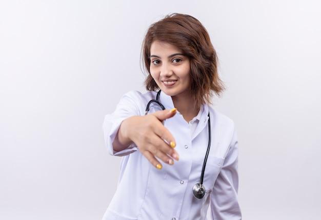 Jonge vrouw arts in witte laag met stethoscoop die zelfverzekerde groet glimlachen die een hand aanbieden die zich over witte muur bevindt