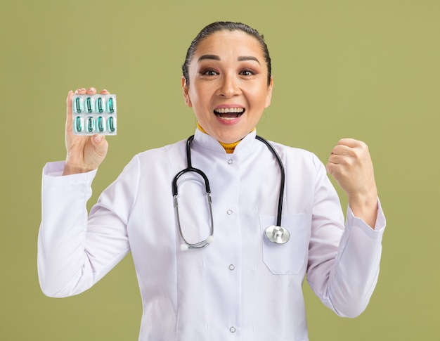 Jonge vrouw arts in witte medicijnjas met stethoscoop om nek met blaar met pillen balde vuist blij en opgewonden staande over groene muur