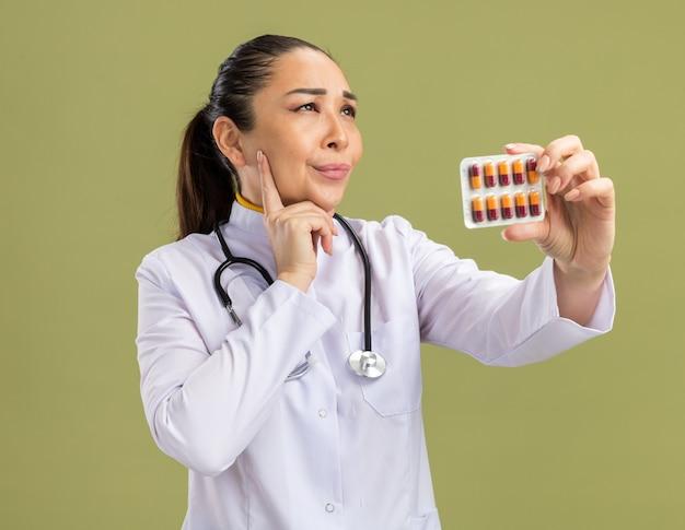 Jonge vrouw arts in witte medicijnjas met stethoscoop om nek met blaar met pillen opzij kijkend verbaasd over groene muur