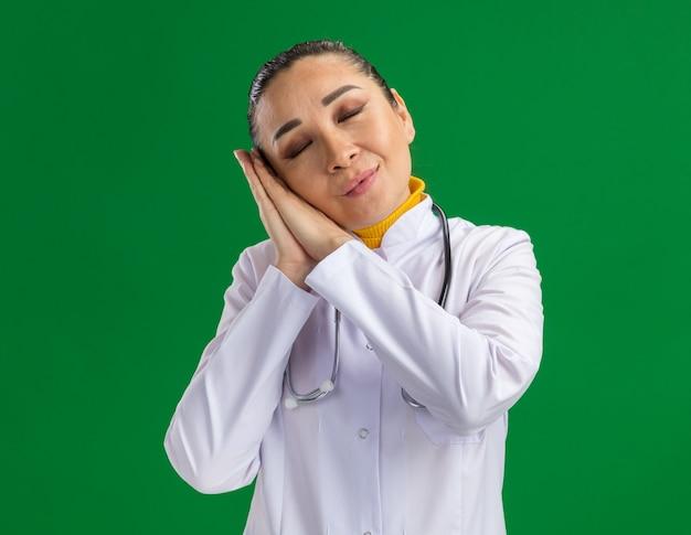 Jonge vrouw arts in witte medicijnjas met stethoscoop rond nek handpalmen bij elkaar houden slaap gebaar maken hoofd leunend op handpalmen permanent over groene muur