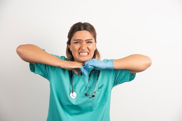 Jonge vrouw arts latex handschoenen en scrubs dragen op witte achtergrond.