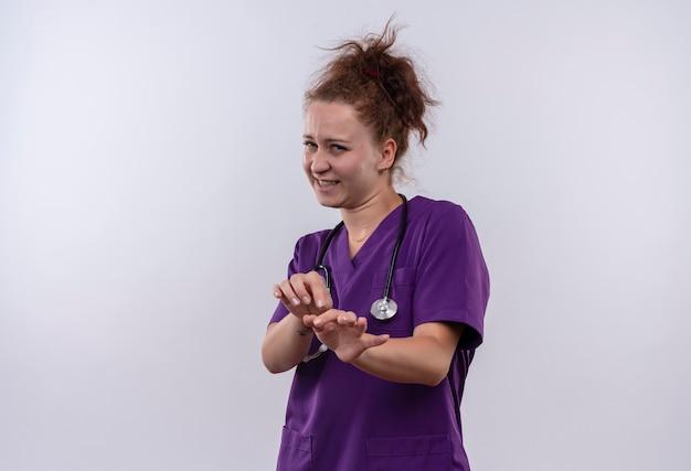 Jonge vrouw arts medische uniform met stethoscoop dragen defensie gebaar met handen met walgen uitdrukking staande over witte muur