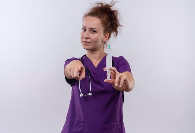 Jonge vrouw arts medische uniform met stethoscoop houden spuit wijzend met vinger kijken met ernstig gezicht staande over witte muur
