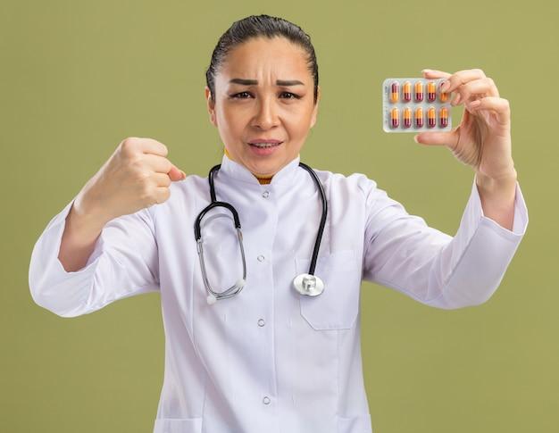 Jonge vrouw arts met blaar met pillen balde vuist met ernstig gezicht