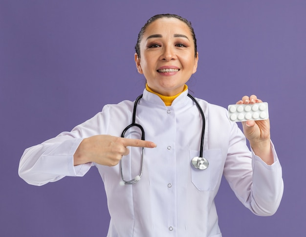 Jonge vrouw arts met blaar met pillen wijzend met wijsvinger ernaar glimlachend zelfverzekerd