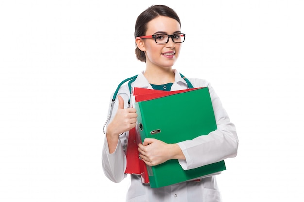 Jonge vrouw arts met de bindmiddelen van de stethoscoopholding in haar handen met duim omhoog in witte eenvormig op wit