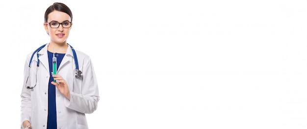 Jonge vrouw arts met de spuit van de stethoscoopholding in witte eenvormig op wit