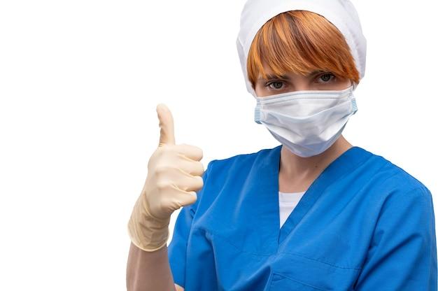 Jonge vrouw arts met een medisch masker op haar gezicht verschijnt duim