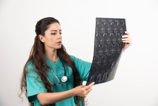 Jonge vrouw arts op zoek op x-ray over witte muur.