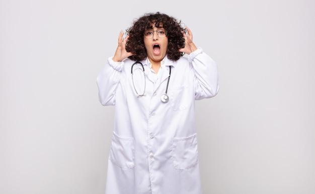 Jonge vrouw arts schreeuwen met handen in de lucht, woedend, gefrustreerd, gestrest en boos