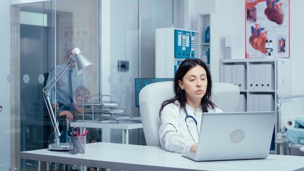Jonge vrouw arts typen op laptop in moderne privékliniek. patiënten en artsen op de achtergrond over glazen wand en verpleegster die naar röntgenstralen kijkt. zorgsysteem concept verzorgen, overleg in hos