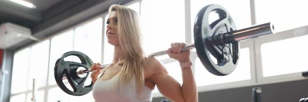Jonge vrouw atleet squats doen met een barbell barbell squat techniek gewicht selectie en