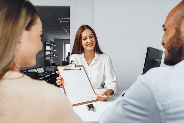Jonge vrouw auto verkoper contract tonen aan paar autokopers in haar kantoor