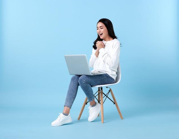 Jonge vrouw aziatische gelukkig lachend in casual wit vest met denim jeans. blauwe ruimte.