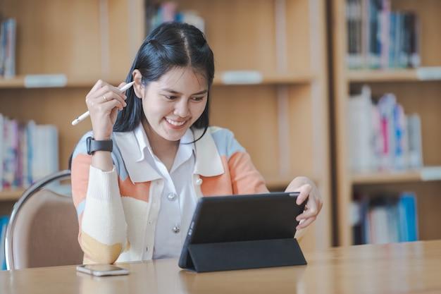 Jonge vrouw aziatische student in studentenuniform die online studeert, een boek leest, digitale tablet of laptop gebruikt in de universiteitsbibliotheek terwijl het klaslokaal wordt beperkt tijdens de covid-19-pandemie