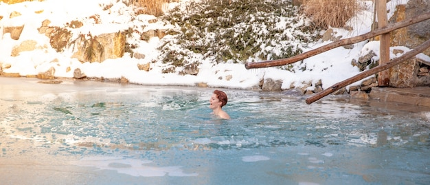 Jonge vrouw baden in een bevroren meer na sauna