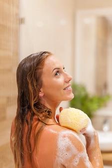 Jonge vrouw badend onder de douche