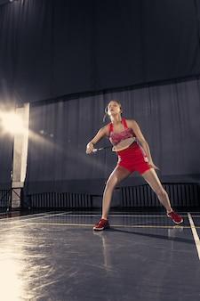 Jonge vrouw badminton spelen op sportschool