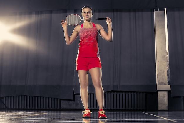Jonge vrouw badminton spelen over gymruimte