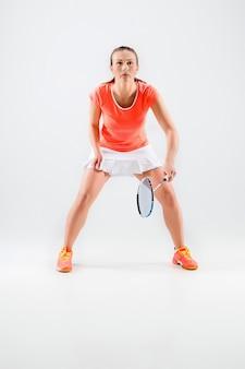 Jonge vrouw badminton spelen over wit
