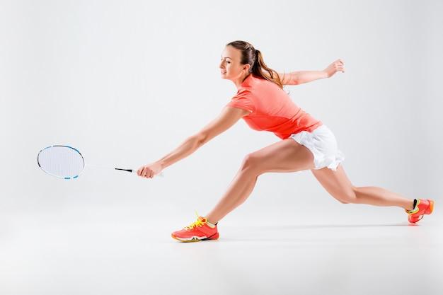 Jonge vrouw badminton spelen over witte muur