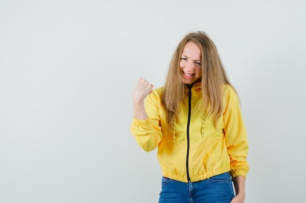 Jonge vrouw balde vuist in geel bomberjack en blauwe jean en op zoek uitgeput, vooraanzicht.