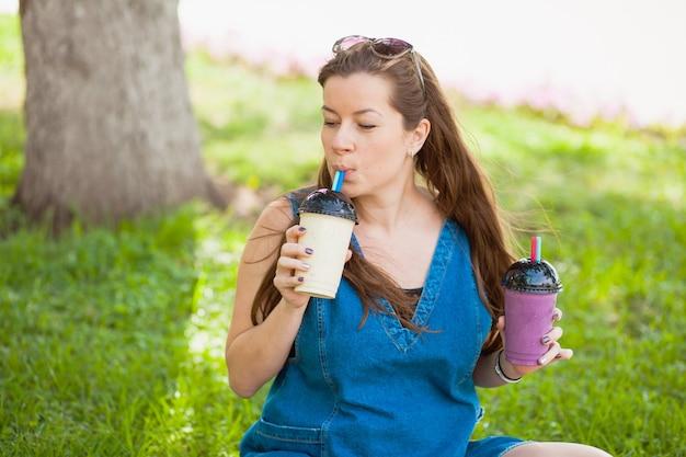 Jonge vrouw banaan smoothie drinken in een park. lekkere milkshake. gezond levensstijlconcept
