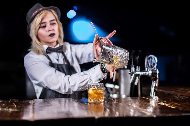 Jonge vrouw barkeeper toont het proces van het maken van een cocktail in de nachtclub
