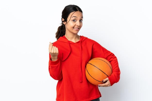 Jonge vrouw basketbal spelen over geïsoleerd wit geld gebaar maken