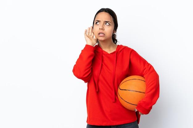 Jonge vrouw basketbal spelen over geïsoleerd wit luisteren naar iets door hand op het oor te leggen