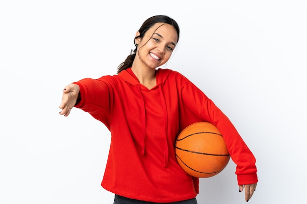 Jonge vrouw basketbal spelen over geïsoleerd wit presenteren en uitnodigen om met de hand te komen