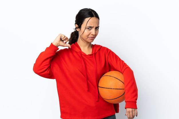 Jonge vrouw basketbal spelen over geïsoleerd wit trots en zelfvoldaan