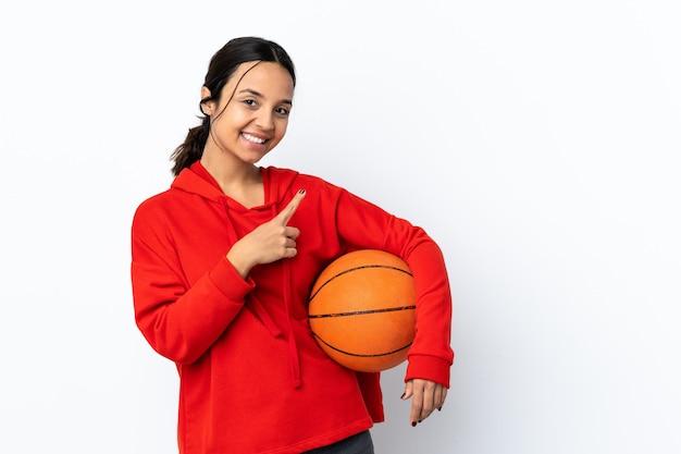 Jonge vrouw basketbal spelen over geïsoleerd wit wijzend naar de kant om een product te presenteren