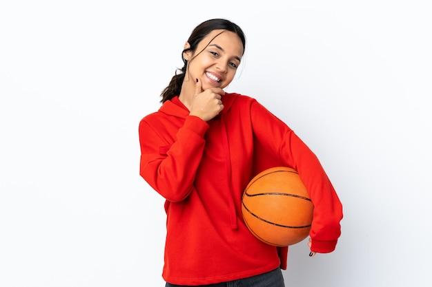 Jonge vrouw basketbal spelen over geïsoleerde wit blij en lachend