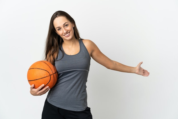 Jonge vrouw basketbal spelen over geïsoleerde witte achtergrond handen uitbreiden naar de zijkant voor uitnodigend om te komen