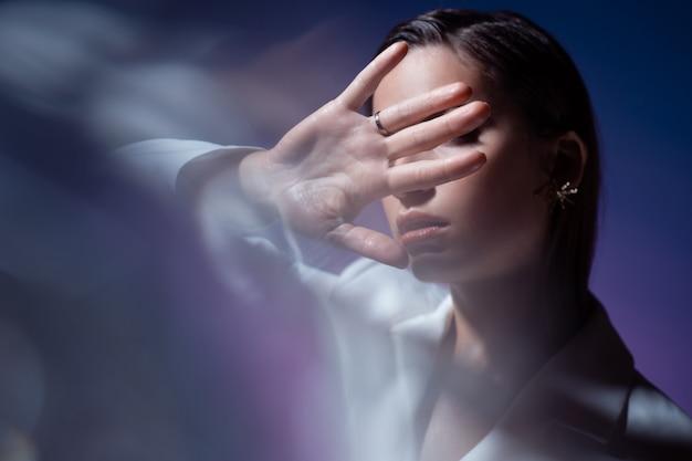 Jonge vrouw bedekt haar gezicht met haar handen, verbergt zich en zegt stop. stijlvolle modieuze jonge vrouw in het wit, portret met optische flitsen.