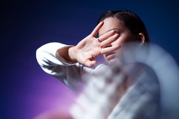 Jonge vrouw bedekt haar gezicht met haar handen verbergt zich en zegt stop