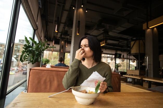 Jonge vrouw bedekt haar neus vanwege slecht ruikend voedsel.