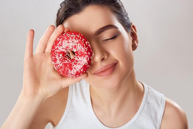 Jonge vrouw bedekte haar gezicht met roze dessert in huiskeuken. donkerbruin meisje proeft een toetje. snoepjes zijn ongezond junkfood.