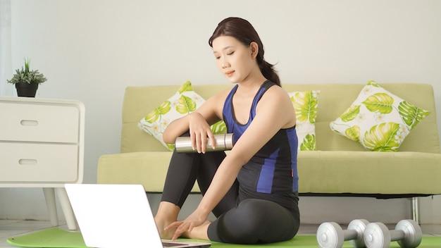 Jonge vrouw beëindigt yogabeoefening en kijkt naar laptopscherm